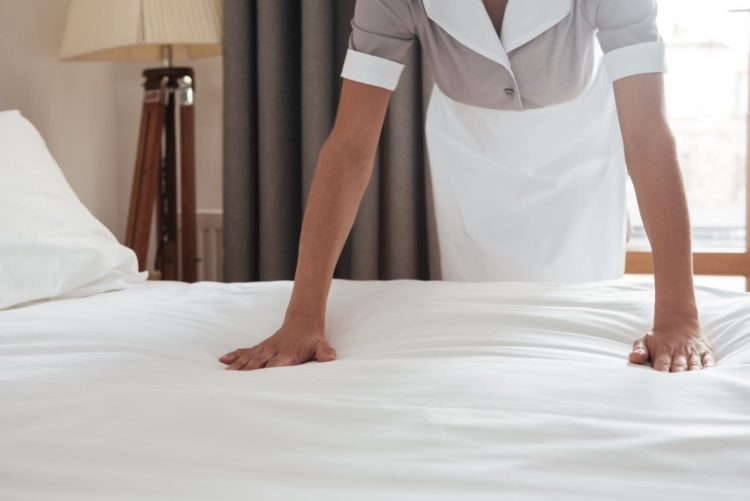 Hotel maid changing the bedsheets - Avoiding bed bugs