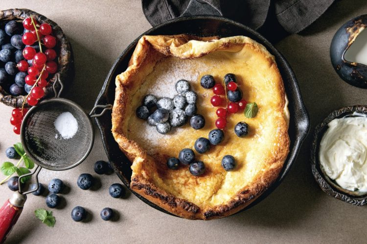 Dutch baby with berries in a seasoned cast iron pan