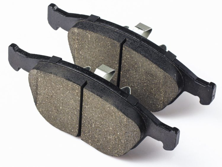 Two brake pads for disc brakes of car on a white background. Spare parts for car maintenance, brake system consumables.