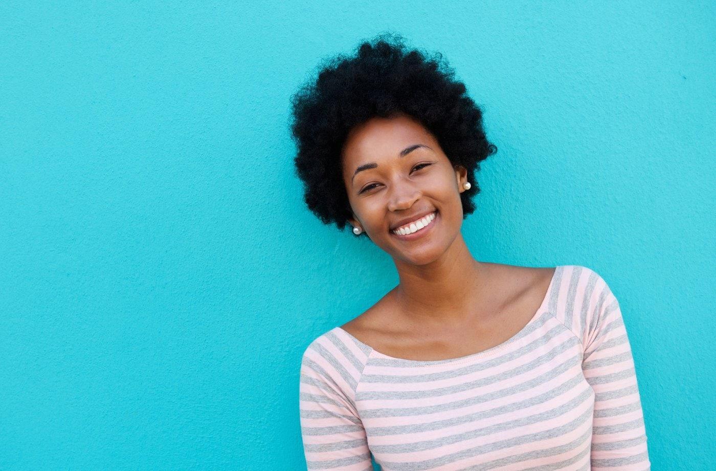 Pretty smiling woman standing against aqua wall