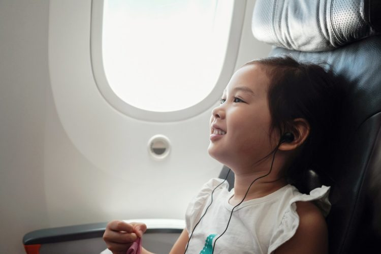 Little girl flying on a plane listening to music