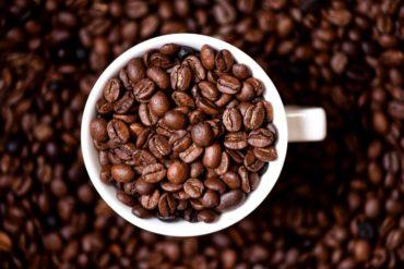 Coffee mug filled with dark coffee beans