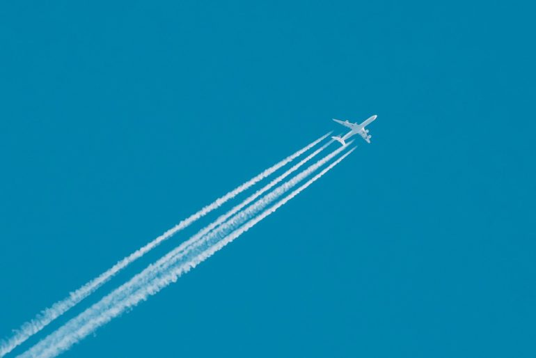 Jet plane flying with white trails from engines