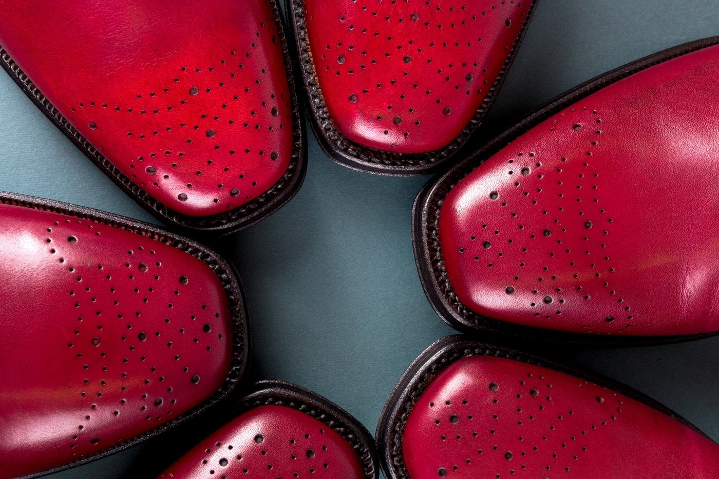 Many pairs of red leather Oxford shoes