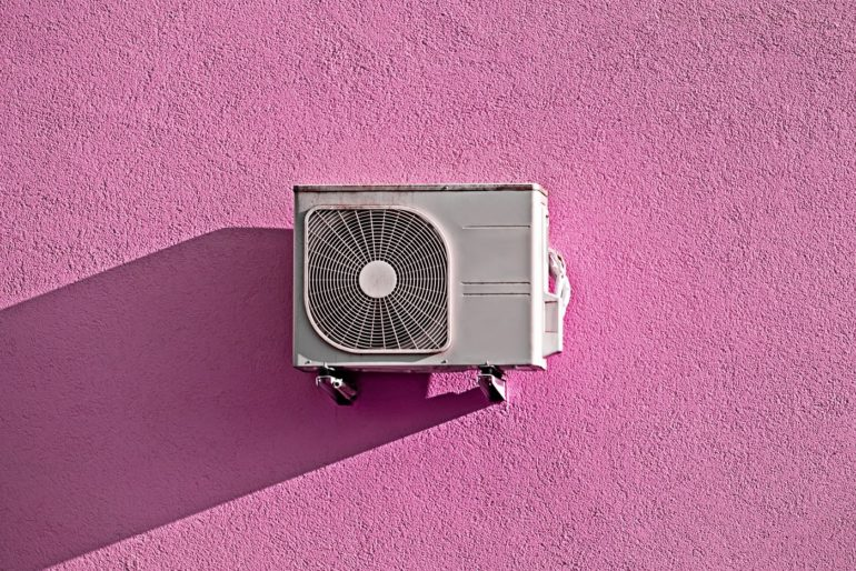 Air conditioning unit on pink stucco