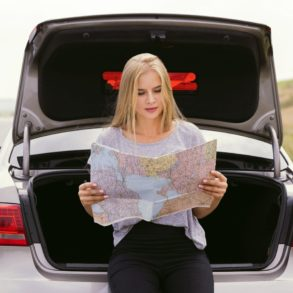 Woman reading a map leaning on trunk
