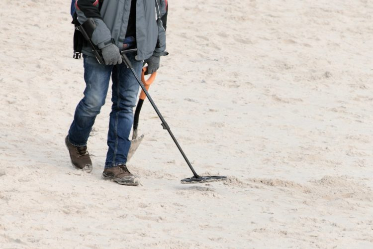 Man walking the beach with a metal detector