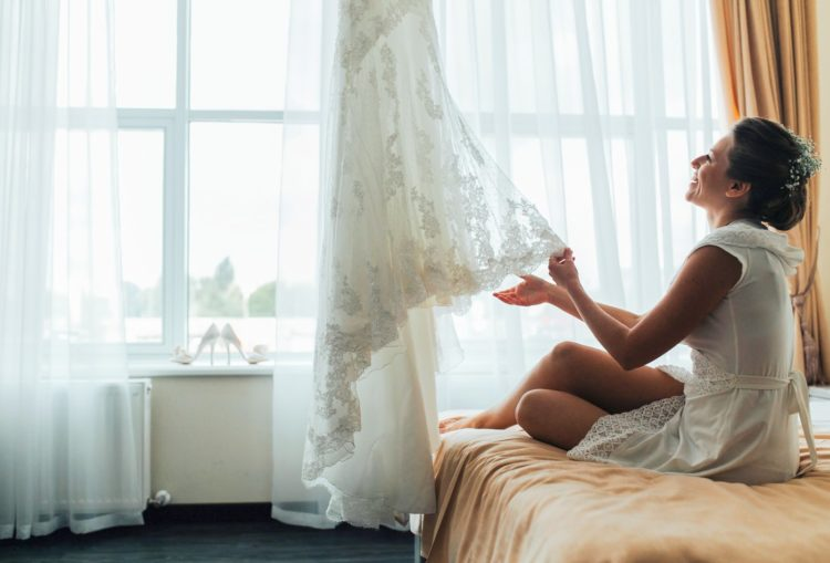 Woman looking at the lace of her wedding dress