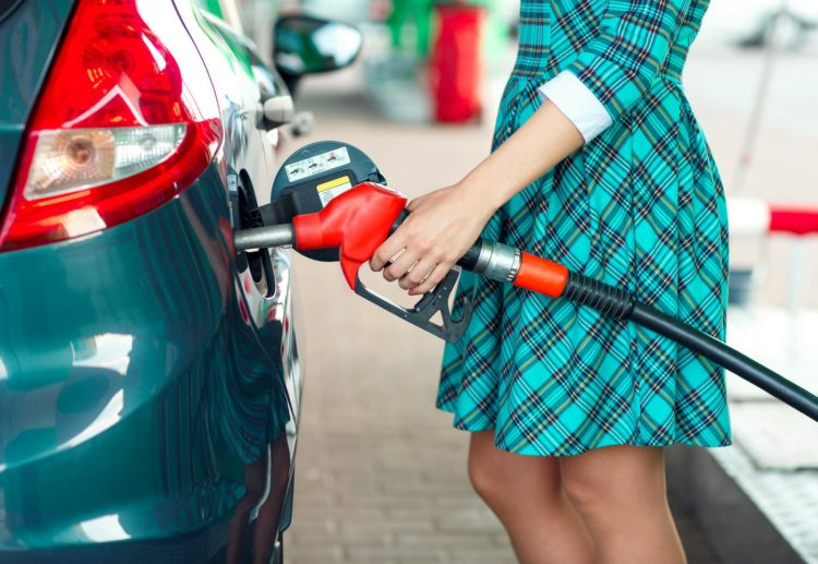 Woman filling car up with gas at self-service station