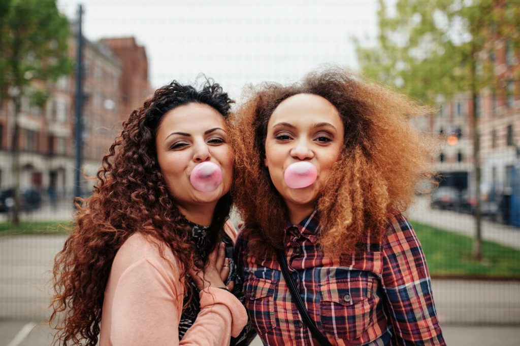Women blowing bubbles with chewing gum