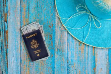 USA passport and dollar banknotes with blue hat preparation for traveling