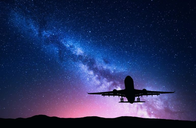Airplane taking off against a starry background