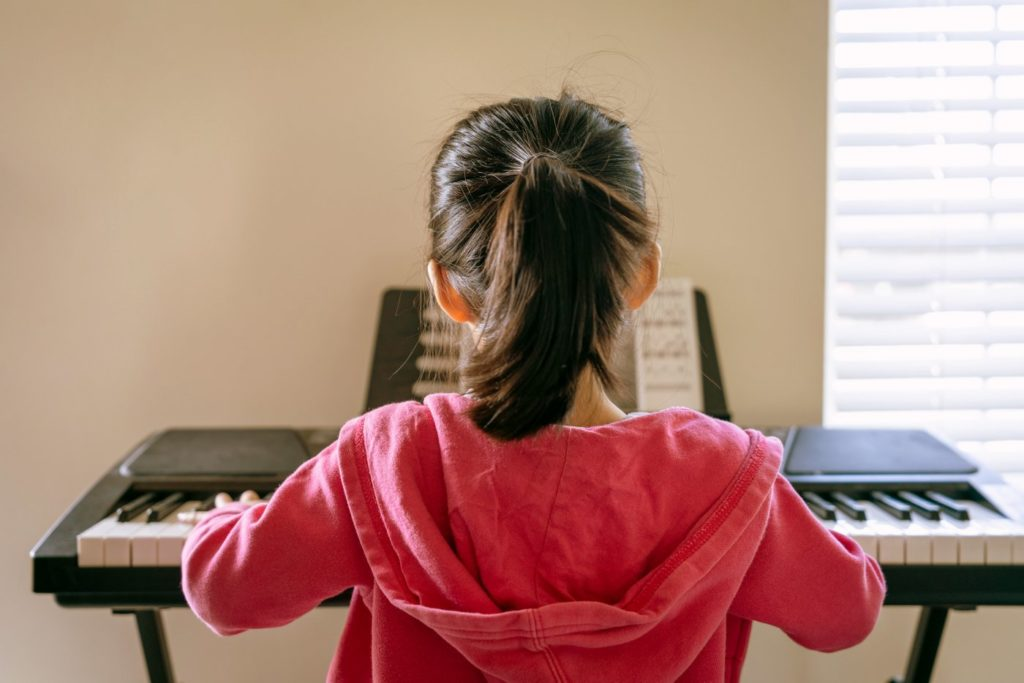 Girl playing piano keyboard musical instrument
