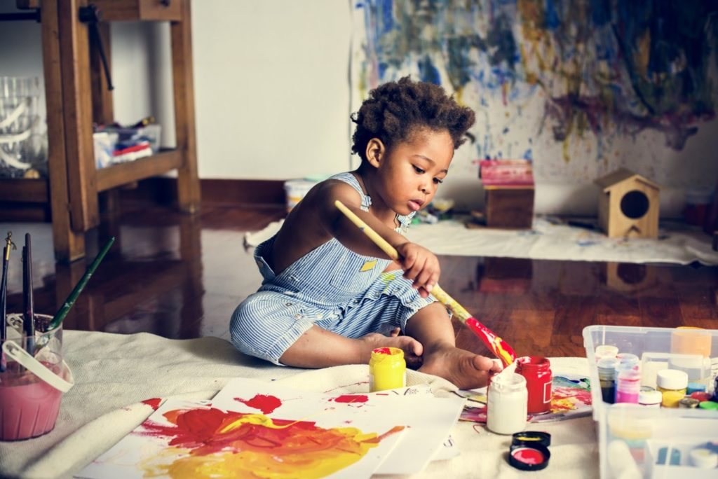 Young boy painting on a big canvas